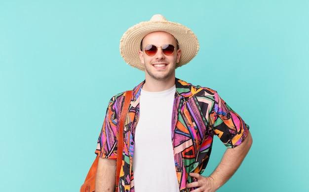 Homme de tourisme souriant joyeusement avec une main sur la hanche et une attitude confiante, positive, fière et amicale