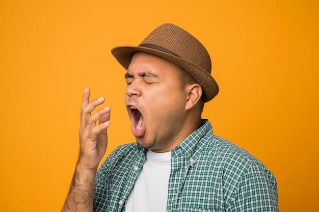 Homme de tourisme en vacances ennuyé bâillement fatigué couvrant la bouche avec la main isolé sur jaune