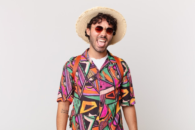 Homme de touriste hispanique avec une attitude joyeuse, insouciante et rebelle, plaisantant et sortant la langue, s'amusant