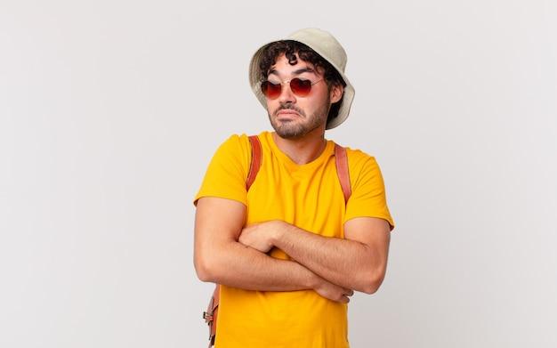 Homme de touriste hispanique haussant les épaules, se sentant confus et incertain, doutant des bras croisés et regard perplexe