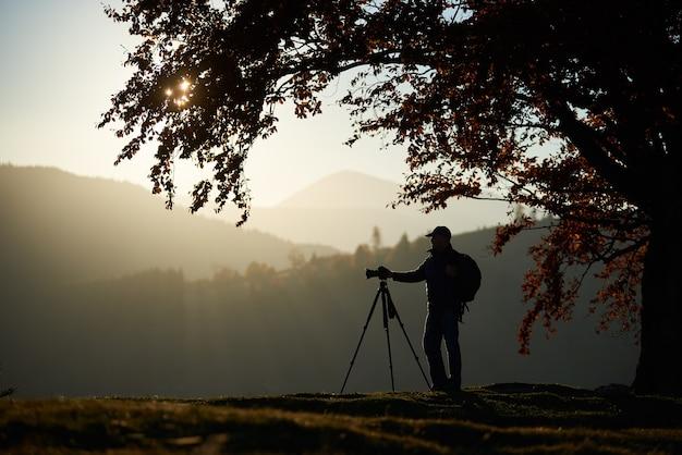 Homme de touriste randonneur avec caméra sur vallée herbeuse sur fond de paysage de montagne sous grand arbre.