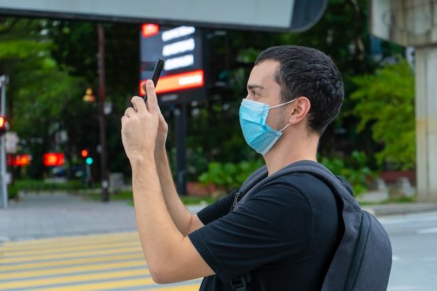 Un homme touriste avec un sac à dos sur le dos et un masque chirurgical sur le visage, photographie des bâtiments dans une rue de la ville. pandémie de coronavirus. implications pour le tourisme.