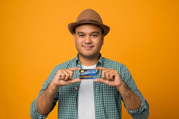 Homme de touriste en vacances tenant une carte de crédit isolée sur jaune