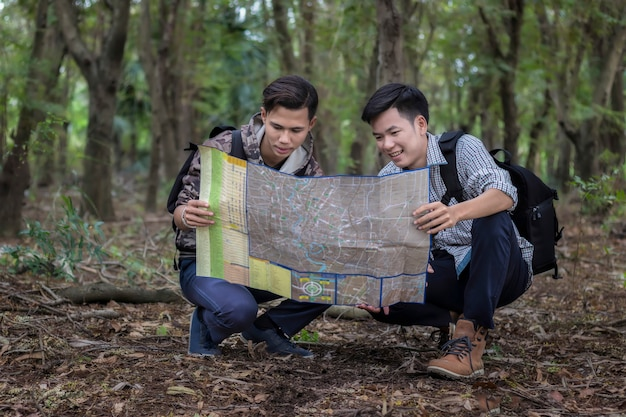 Un homme touristes avec sac à dos à la forêt en regardant la carte pour apprendre les sentiers de randonnée.
