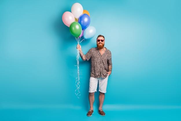 Homme touristique barbu rousse funky tenir des montgolfières
