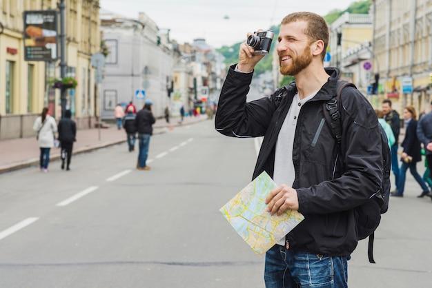 Homme touristique avec carte et appareil photo