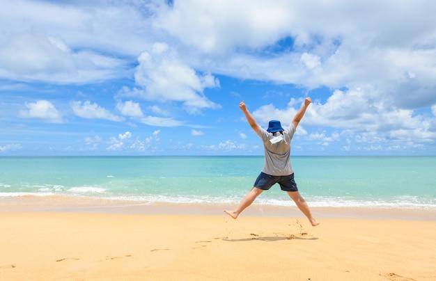 Un homme touristique heureux et énergique accroche des masques faciaux et saute à la plage pendant les vacances d'été, du plaisir et de la liberté avec de nouveaux concepts de voyage normaux