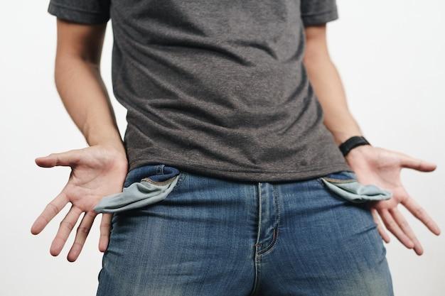 Homme tournant la poche de jean pour montrer la poche vide. faillite, mauvaise économie, pas de concept d'argent.