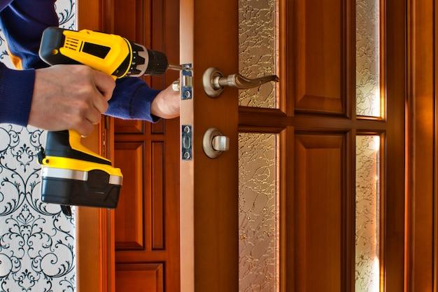 Un homme avec un tournevis à la main répare la serrure de la porte
