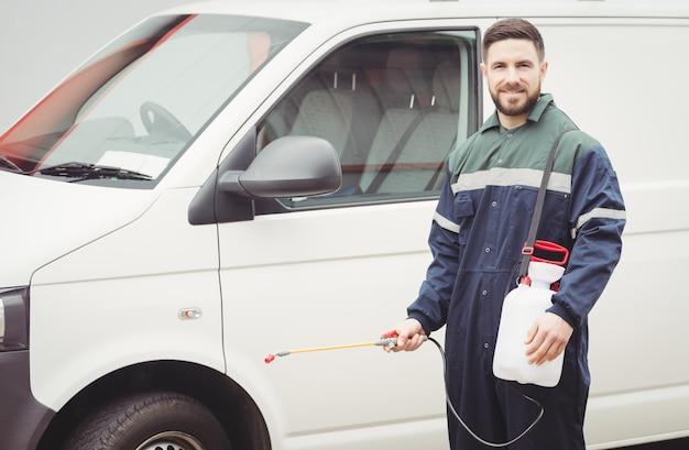 Homme à tout faire avec un insecticide debout devant sa camionnette