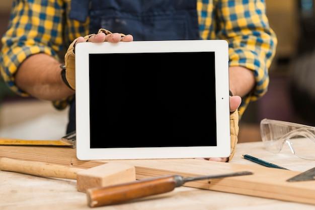 Homme à tout faire montrant une tablette numérique avec un écran blanc sur un établi