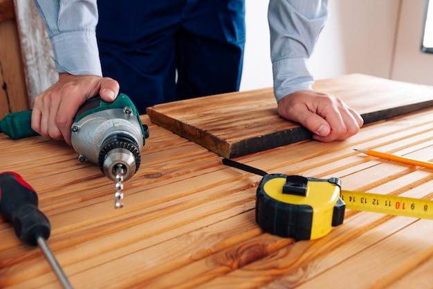 Un homme à tout faire en uniforme bleu travaille avec de l'électricité conception de rénovation de maison de tournevis automatique
