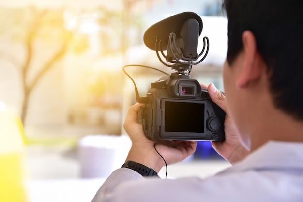 Homme en train de filmer vdo en reflex numérique