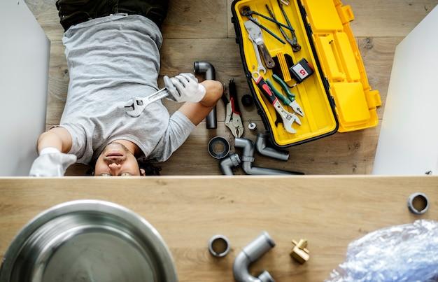 Homme en train de réparer un évier