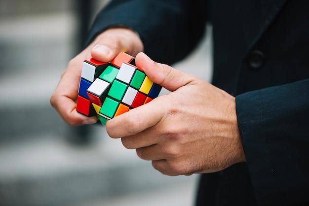 Homme en train de résoudre le cube de rubik