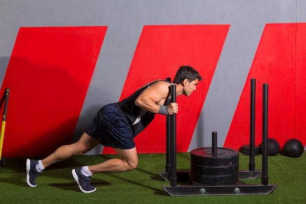 Homme de traîneau poussant exercice de musculation poids