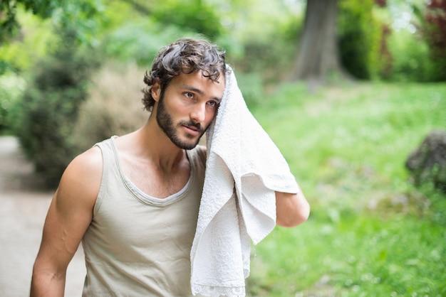 Homme transpirant après une séance d'entraînement dans un parc