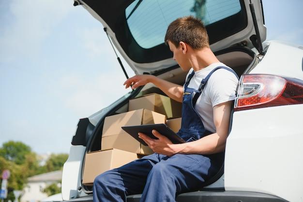 Un homme transportant un colis depuis une voiture de livraison - concept de service de messagerie