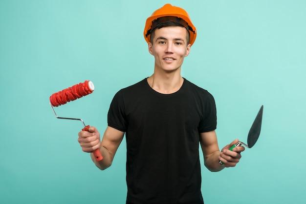 Homme de travail asiatique dans un casque orange se dresse avec un rouleau à peinture et une truelle sur un fond bleu