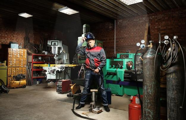 L'homme De Travail Est Un Soudeur En Masque, Produit Métallique Au Garage à La Maison, Avec Soudage Au Gaz Brûlant à La Flamme Photo Premium