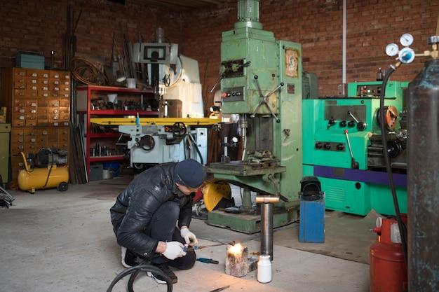 L'homme de travail est un soudeur en masque, produit métallique au garage à la maison, avec soudage au gaz brûlant à la flamme