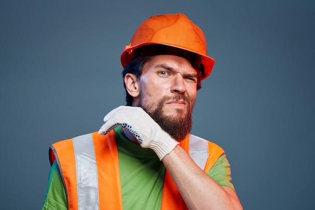 Homme de travail posant avec un casque orange
