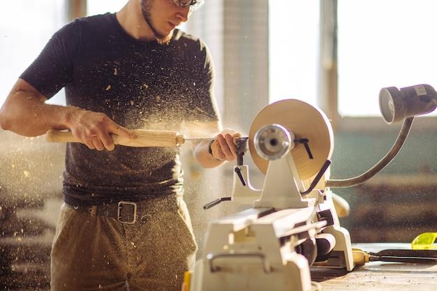 Homme travaillant au petit tour à bois, un artisan sculpte un morceau de bois