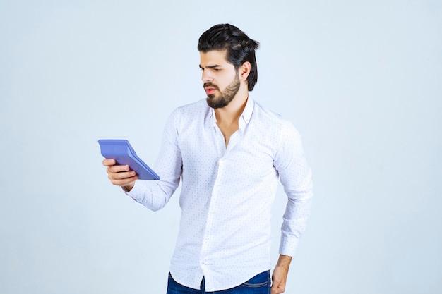 L'homme travaillant avec une calculatrice a l'air confus et réfléchi.