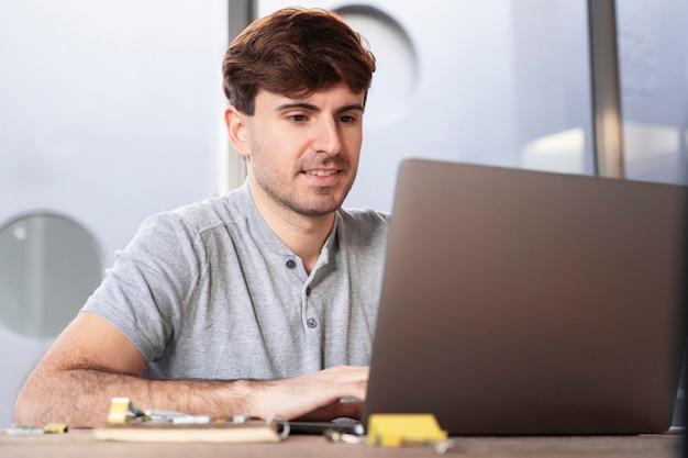 Homme travaillant comme pigiste à la maison sur son ordinateur portable