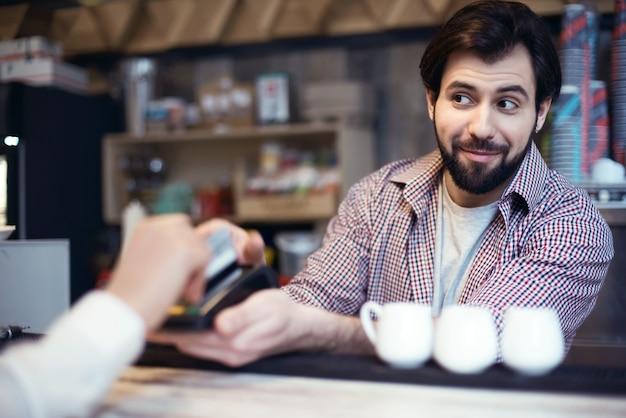 Homme travaillant dans un café prenant le paiement sans numéraire