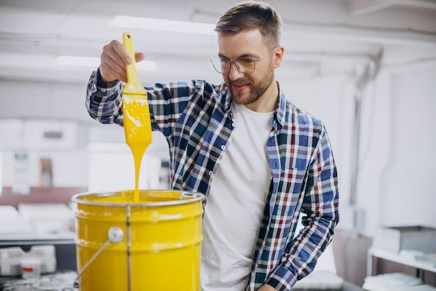 Homme travaillant dans une imprimerie avec du papier et des peintures