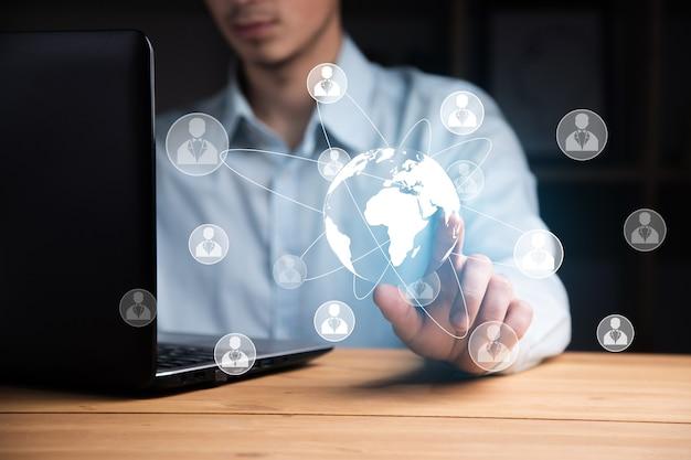 Homme travaillant dans un ordinateur avec un réseau mondial et social