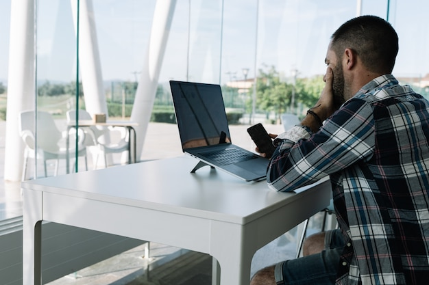 Homme travaillant devant l'ordinateur portable et avec un mobile à la main dans un espace de travail