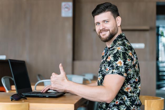 Homme travaillant à distance avec un ordinateur portable et tournant la tête sur le côté tout en faisant des gestes avec sa main pour être bien