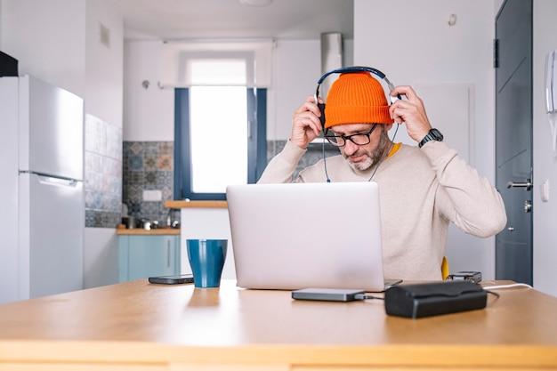 Homme travaillant à domicile sur un ordinateur portable assis à un bureau surfer sur internet