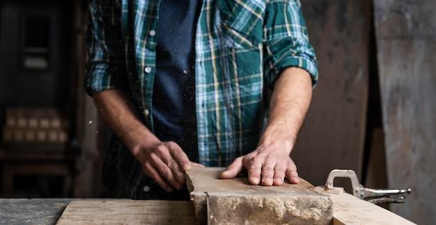 Homme travaillant avec du bois en atelier