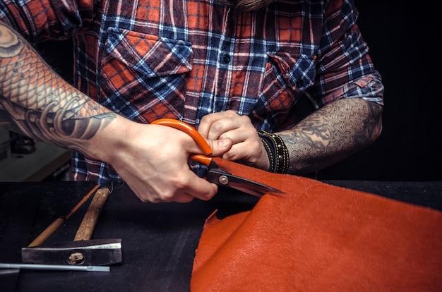 Homme travaillant avec du cuir à l'aide de ciseaux d'artisanat