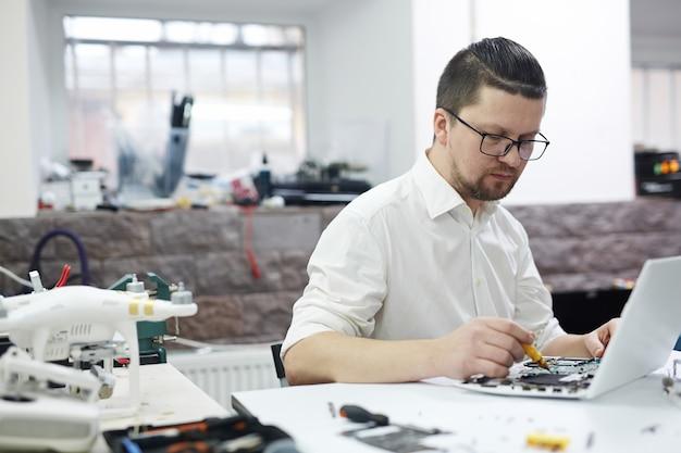 Homme travaillant avec l'électronique