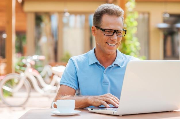 Homme travaillant à l'extérieur. homme mûr gai travaillant à l'ordinateur portable et souriant tout en s'asseyant à la table dehors avec la maison à l'arrière-plan