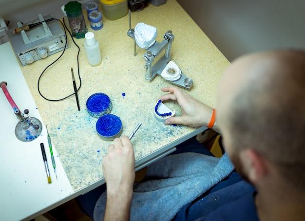 Homme travaillant sur de fausses dents dans son atelier