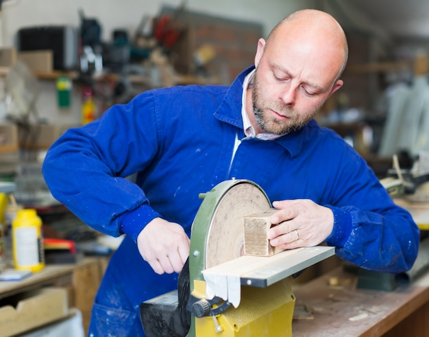 Homme travaillant sur une machine à l'atelier de bois