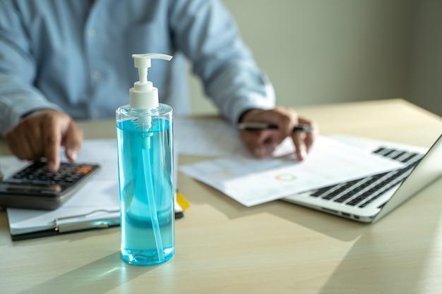 Un homme travaillant à la maison lockdown covid 19 coronavirus utilisant un gel antiseptique à distance sociale covid19 vaccin coronavirus
