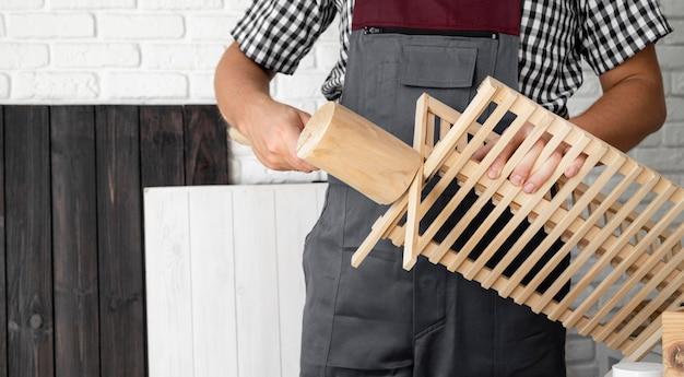 Homme travaillant sur un objet en bois avec gros plan