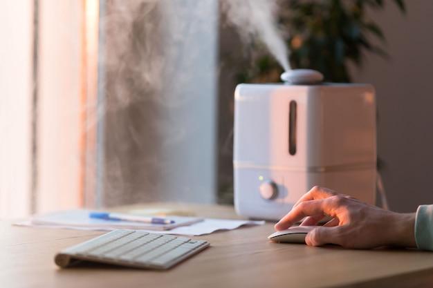 Homme travaillant sur ordinateur, à l'aide de souris pc près du diffuseur d'huile d'arôme sur la table, vapeur de l'humidificateur d'air, mise au point sélective