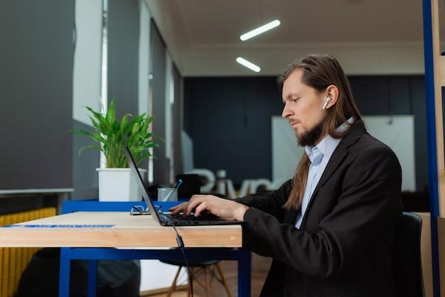 Un homme travaillant sur un ordinateur portable au bureau