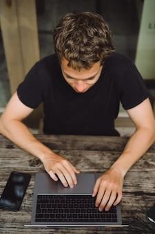 Homme travaillant avec un ordinateur portable dans un café sur une table en bois