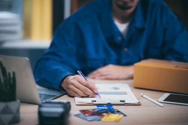 L'homme travaillant un ordinateur portable à domicile sur un plancher en bois avec colis postal, concept d'idées de vente en ligne.