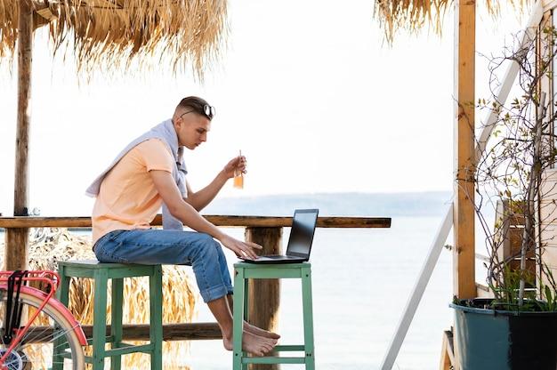 Homme travaillant sur un ordinateur portable à l'extérieur plein coup