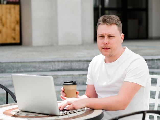 Homme travaillant sur un ordinateur portable à l'extérieur tout en buvant un café