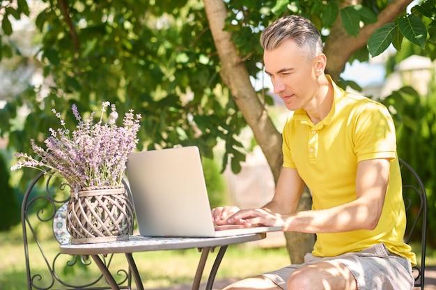 Homme travaillant sur ordinateur portable à la maison dans le jardin